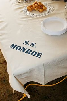 Simple table cloth for a nautical party. Plain muslin with navy paint and stenciled letters... lovely!