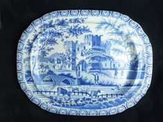 OnlineGalleries.com - A Large 19th century Meat Plate, the rounded rectangular rim with scallop edges, and a dished profile, the edge decorated with enclosed shells alternating with stylised lilies. The body decorated with a scene of a large semi ruined castle/abbey with a town scape and hills beyond. The foreground with a bridge over a lake with cattle watering, and people in conversation, a cattle herder and a man on horse back riding over the bridge