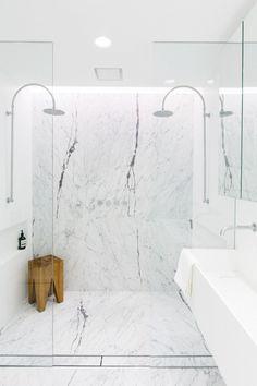 Modern bathroom an open marble shower, and a wooden shower stool