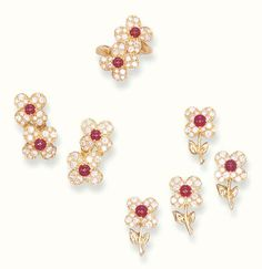 A SET OF DIAMOND AND RUBY JEWELLERY, BY VAN CLEEF & ARPELS   Comprising a ring of crossover design, set with two circular-cut diamond flowerheads to the cabochon ruby centre; a pair of ear clips and three clip brooches en suite  Signed Van Cleef & Arpels, nos 65185G60, B3079671, B1206G143, B1206G106, B1206G153 and B1206G98