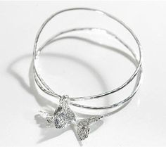 Two strands of silver intertwine for a look of pure elegance, complimented by two butterfly charms.  Handmade in Britain, sterling silver bangle.
