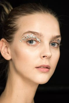 Silver metal leaf (not tinfoil) was applied to the eyelids on models at Holly Fulton for the ultimate party peepers. The MAC team used Mixing Medium Eyeliner in the socket first, with adhesive through the crease before dabbing on the embellishment.    - Cosmopolitan.co.uk
