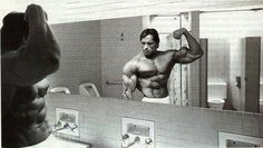 ILYKS.COM - Arnold Schwarzenegger in the bathroom shirtless flexing his bicep he looks really lean Showing his left gun