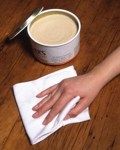 Choose paste wax, the solid kind sold in tins. Natural (clear) wax works on any wood, but dark wood may benefit from tinted wax (it will mask tiny scratches). Begin by cleaning with a mild solvent, such as mineral spirits (test first in a hidden spot).Then cover the piece with a thin, even layer of wax using a cotton rag or cheesecloth. Let dry 10 to 25 minutes; buff vigorously.