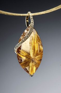 A modern pendant design by Adam Neeley.  Little Star Rutilated Quartz Pendant is distinctive and sweet. In this unique pendant design, a carefully selected slice of rutilated quartz, showcasing a starburst pattern in rutile, is set in yellow gold with col