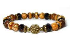 Beautiful brown beaded nature bracelet made with 8mm picture jasper gemstones, robles wood, czech crystals and a pretty bronze toned detailed flower focal bead. This looks great with just about everyt