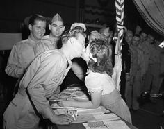Shirley Temple kisses the troops for charity during World War II, 1940s.