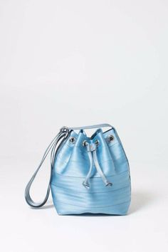 """Bucket shaped horizontally stitched seatbelt. Fully lined with inner zip pocket and extra slip pockets for storage. Features cross body strap drawstring and/or magnetic snap closure.  Measures: 9"""" (L) X 11"""" (H) X 5.5"""" (W) Adjustable strap extends from 25"""" - 51""""  Bucket Sky Blue by Harvey's Seatbelt Bags. Bags - Bucket Omaha Nebraska"""