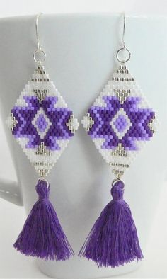 This earring design was created using brick stitch and ladder stitch to create a boho/tribal design. 6 lb. fireline was used to bead the silver, light purple, and ultra violet purple, and white miyuki 11/0 delica seed beads, so the earring shape is strong, but are almost weightless
