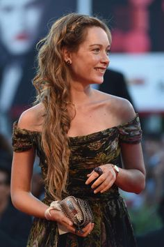 Cristiana Capotondi's beautiful braid:  To make this hairstyle, combing hair and passes a texturizing product that helps to maintain the hairstyle. Pass them quickly with the iron to create gentle waves. Her hair to the side, fasten them with paper clips hidden in her hair. Make the braid from the top. Hide it between the strands.