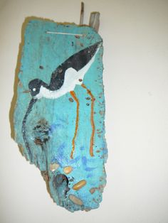 Bird painted on driftwood, pebles on it to