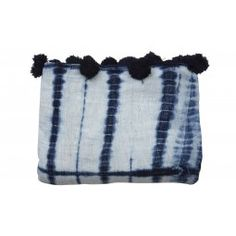 Our Indigo Brique Coverlet  is part of a collection that we designed in partnership with a women's cooperative in the West African country of Mali. It is made completely by hand, start to finish. The members are trained in the textile arts — from spinning yarn from locally sourced cotton, to weaving the fabric, then dying with indigo in the graphic bogolan style and finally sewing the finished product. Our Indigo Brique Coverlet is delightfully embellished with pompom trim…