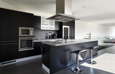 Stunning modern kitchen with black cabinets, and big island with concrete bench top, cooking elements and overhead vent
