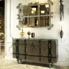 35H x 62W x 12D Hand made iron console reminiscent of antique valise with iron strapping and decorative bolts Body is hand painted in silver with distressing in bronze tones Lock includes key, although console does not open Glass 1/2/ top with 48 degree ... - $3655.00
