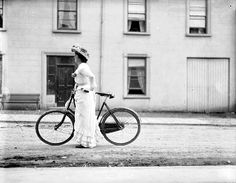 Woman with bicycle, somewhere between 1890 and 1910