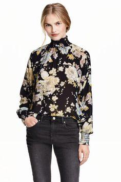 Blusa floral de gasa: Blusa ancha de gasa con estampado floral. Cuello elevado y fruncido, mangas largas raglán con puños fruncidos, abertura en la espalda y cierre en la nuca.
