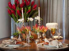 mesa posta jantar a luz de velas com flores tropicais.