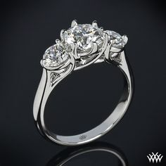"Brilliantly designed, the ""Butterflies"" 3 Stone Engagement Ring incorporates sweeping lines that twist to create one unforgettable ring. You can choose to purchase this ring as a setting only which will allow you to select all three diamonds or we can provide you with two A CUT ABOVE® Hearts and Arrows Diamond Melee side stones (0.50ctw"