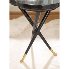 Clover-shaped tabletop set on a tripod base detailed with leather fittings. Finished with metal paw-feet sabots, leafed in gold.