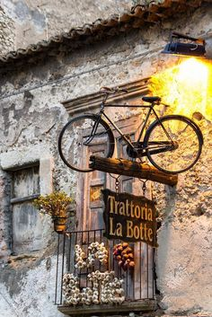 Bicycle used above a travern sign in Tropea, province of Vibo Valentia, Calabria region Italy Calabria Italy, Tropea Italy, Sardinia Italy, Web Banner Design, Purple Home, Lokal, Shop Fronts, Store Signs, Belle Photo
