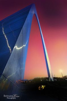 Blue Saint Louis Arch with pink and purple skies.