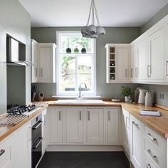White and sage green kitchen with wall cupboards