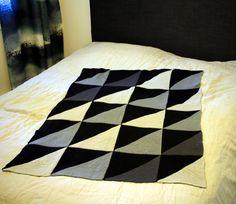 Harmaasävyisistä kolmioista koostuva Lodicula-peitto levitettynä sängylle.