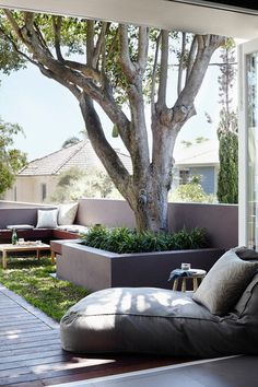 Beach Style Landscape by Harrison's Landscaping. Shaded lounge. A courtyard garden with just a hint of grass makes for a relaxed and inviting space for chatting, reading or napping beneath the shade of a mature tree. The low wall doubles as a backrest for the built-in bench and ties the courtyard in with the design of the house.