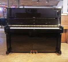 A 1998, Steinway Model V upright piano with a black case and brass fittings at Besbrode Pianos. Piano has an eighty-eight note keyboard and three pedals.