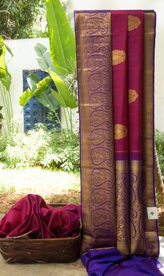 This ethnic purple kanchivaram silk has large gold bhuttas all over. The border and pallu have large mango designs intricately woven in gold zari making it a must for this wedding season