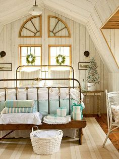 In this coastal master bedroom, soft colors and vintage finds create a cozy, worn feeling. Blue accents bring in a bit of color, and beaded board draws attention to the charming ceiling shape. | myhomeideas.com