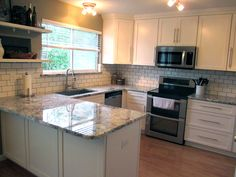 All white shaker kitchen cabinets. Grey granite. Subway tile back splash.
