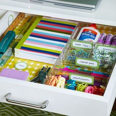 Clear acrylic trays and handwritten labels keep a clutter-prone crafts room drawer neat and tidy. The trays can be picked up and moved around the room as needed, but the labels ensure everything finds its proper home when its time to clean up.