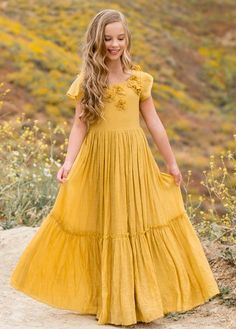This gorgeous maxi dress features beautifully soft rayon and a full, tiered skirt. The bodice is embellished with delicate chiffon flowers for a playful elegance. Fully lined with an invisible zipper closure at the back. Yellow Flower Girl Dresses, Girls Maxi Dresses, Fashion Dresses, Toddler Dress, Baby Dress, Dress Girl, Toddler Outfits, Toddler Girls, Simple Dresses