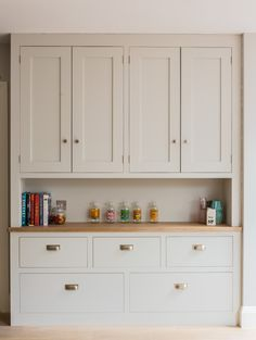 Sustainable Kitchens - Light and Airy Shaker Kitchen in London. Dresser painted in Farrow & Ball Pavilion Grey with two double cupboards and drawers. The worktop is oak and is filled with books and decorative items. Perfect for storage and lesser used items.
