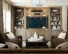 Traditional family room with no fireplace and built-in media and entertainment wall, brown couches and chairs, white accents and a taupe stain on the shelves | Scheinholtz Associates