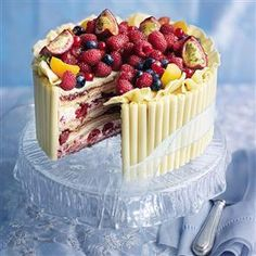 White chocolate and raspberry marquise recipe. This is simply a delicious sponge with cream and fruit, but the decoration makes all the difference. Buy the white chocolate cigarillos (curls) and butterfly bows from Squires