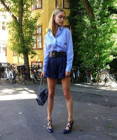 Classic shades of blue–high-wasted belted blue shorts, blue button-down, blue strappy heels, Chanel quilted purse