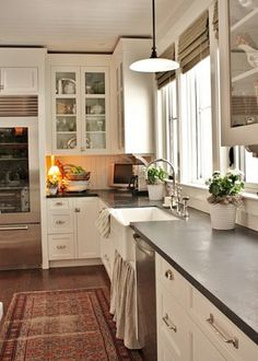 Concrete counter with white cabinets/sink and wood floor
