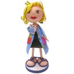 Fofucha caracterizada de profesora, vestida con bata de cuadros y portando regla y unos exámenes.