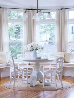 Breathtaking breakfast nook!  I love the bay windows, curtains, and window seating.