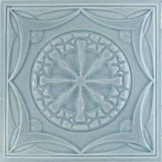 An Art Nouveau partial relief tile with spokes and garland design in pale grey. Condition: one or two minute edge...