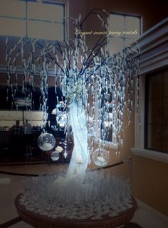 Light up willow tree with glass balls and fresh flowers as a escort card table. Can also be as a centerpiece for wedding, party or any event. www.weddingrentalsonline.com Also on Facebook as Elegant events party rentals.