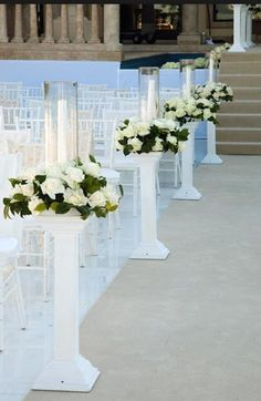 Hurricane lamps with flower rings on white columns