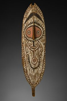 Spirit board, hohao Elema 19th century Wood, pigment H. 129 cm TC 542 Bold circular faces, symmetrical chevron patterns and elaborate eye and navel patterns are the hallmarks of Elema design. This spirit board incorporates all of those features. Each clan had distinctive motifs for spirit boards and shields that were instantly recognizable to members of the community.Oceania