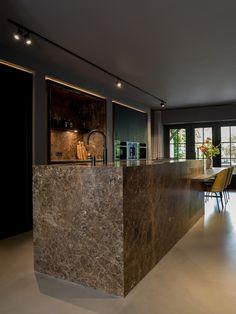 Bij deze keuken is gebruik gemaakt van mooie materialen zoals marmer. De keuken zit vol met bijzondere details, zoals de ledverlichting achter de hoge kasten en het tafelblad dat doorloopt in het marmeren eiland. De drie kastelementen zijn in de wand gebouwd. Er is gekozen om zowel de muren als het plafond een donkere tint te geven. Chic! En het zorgt ervoor dat de grote keukenruimte een intieme uitstraling heeft.   Kitchen Room Design, Kitchen Supplies, Home Kitchens, Luxury Homes, Sweet Home, New Homes, House Design, Interior Design, Architecture