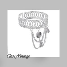 Silver tone arm cuff. Silver tone upper arm cuff. Adorned with chains and charms. Boutique Jewelry Bracelets