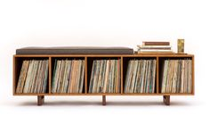 This bench is the ideal solution to having records sitting all over your house and no place to sit. This is an original design, but with a strong influence of Mid Century | Danish Modern. The bench is roughly 67 long, 19 tall (20.5 tall if you include the cushion) and 14 deep. This version of the vinyl storage bench is functionally the same as my other version (the Hi-Fi) but features exposed plywood edges and the cushion is secured to the top of the bench (not hemmed in by a border as in…