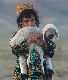 An Afghan girl holds her sheep on the outskirts of Herat on April 10, 2012. (Aref Karimi/AFP/Getty Images)