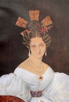 "Known as the ""peineton"" these large and elaborate combs were worn by the fashionable women of Buenos Aires. The illustration is taken from a portrait of Dona Manuela Suarez Lastra de Carmendia by Pellegrini. She wears the dress of the 1830s and a similar comb with upstanding loops which protrude from behind her high fashionable hairdressing."